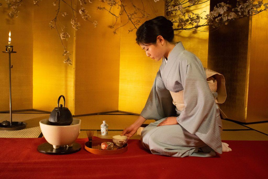 Frau im Kimono bei der Teezeremonie in einem goldenen Zimmer